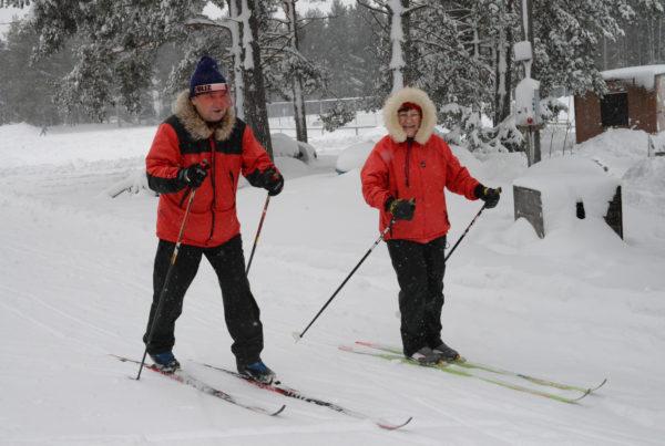 Mies ja nainen hiihtävät perintesellä tyylillä. Taustalla lumisia mäntyjä.