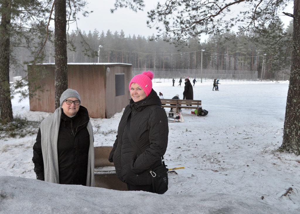 Kaksi naista, taustalla luistelukenttä ja luistelijoita.